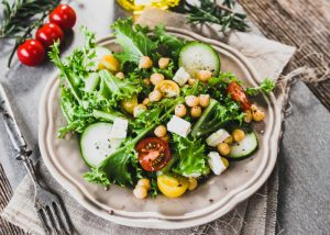 Plate of green salad with cucumbers, greens, tomatoes, and chickpeas on a beautiful grey plate on grey tablecloths
