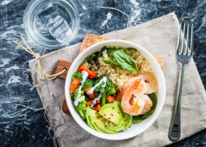 A healthy salad bowl with grains, vegetables, and shrimp, set on a wooden board on a blue marble table with a fork next to it