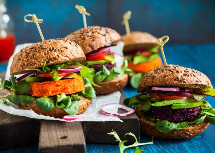 Colorful plant-based burgers set on a wooden board on a blue table