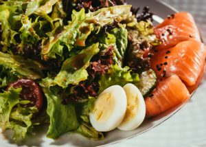 Flexitarian plate of salad greens and dressing, with a few pieces of salmon and two halves of a quail egg
