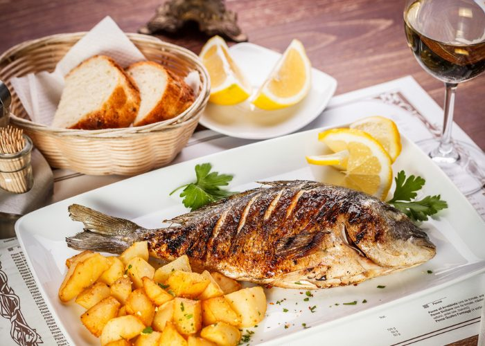 A dinner table with a basket of bread, glass of wine, and a whole grilled fish served on a white plate with a side of roasted potatoes and lemon wedges