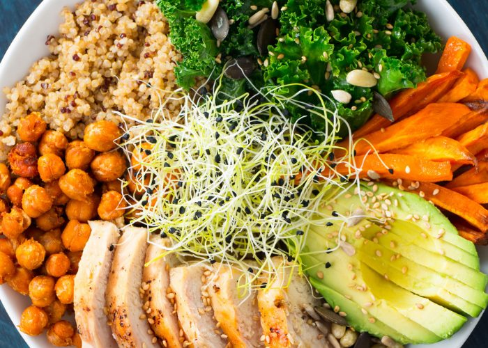 A semi-vegetarian salad bowl with quinoa, chickpeas, avocado, carrots, kale, seeds, alfalfa sprouts, and slices of grilled chicken breast