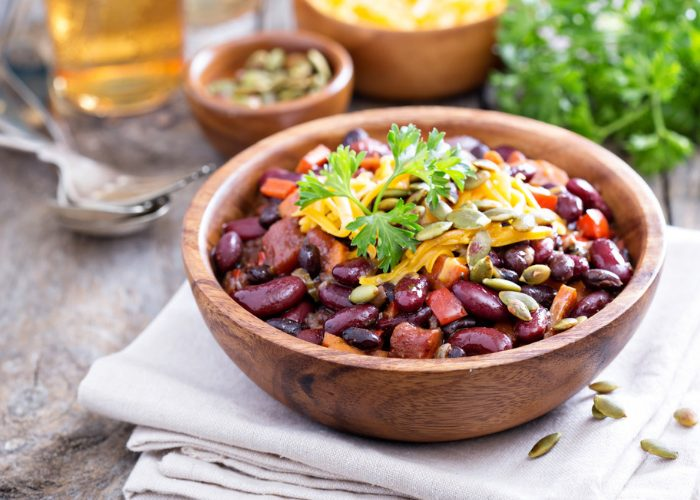 Vegetarian bean chili in a wooden bowl, on a pale tablecloth, on a wooden table with cutlery and ingredients in the background