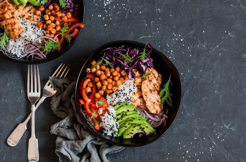 Two bowls of flexitarian salad with grains, vegetables, avocado, some small slices of chicken breast, on a dark grey slate table with two forks beside them
