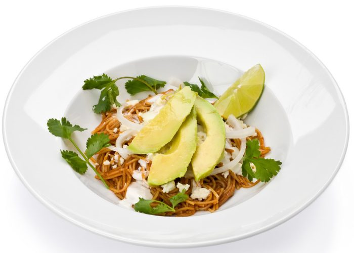 Homemade whole grain pasta topped with avocado and parsley in a large white plate