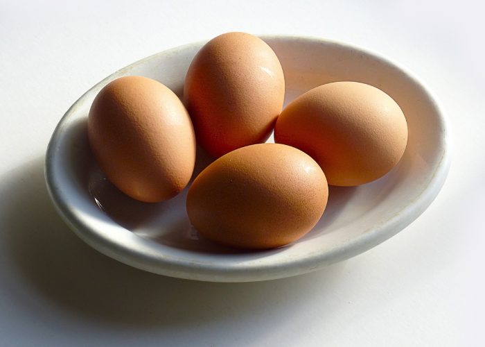 A white bowl with four whole eggs inside