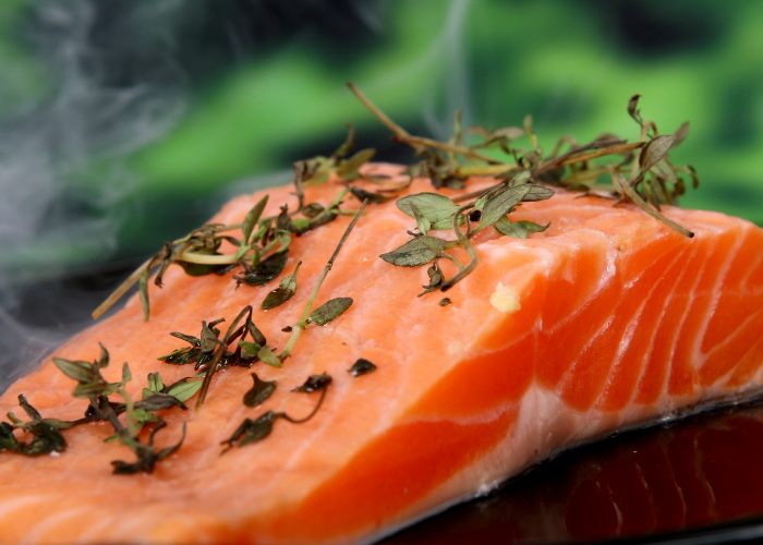 A closeup of raw salmon topped with fresh herbs ready to be put in the oven