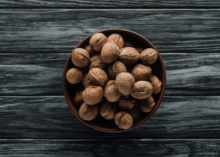 A bowl of whole walnuts on a dark grey wooden table