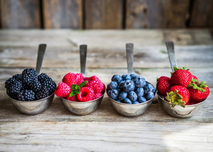 Four different types of berries -  blueberries, raspberries, strawberries, and blackberries - in metal spoons on a wooden table