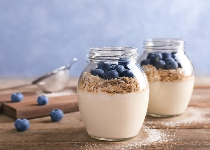Two jars of yogurt topped with oats and blueberries on a wooden table