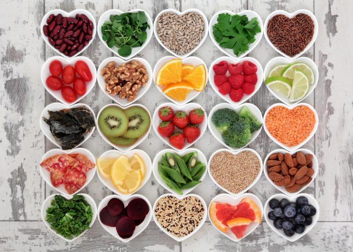 Different healthy foods and vitamins such as fruits, berries, nuts, seeds, and vegetables, in many heart-shaped bowls
