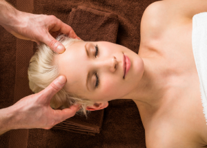 Woman looking relaxed getting a head massage at a spa