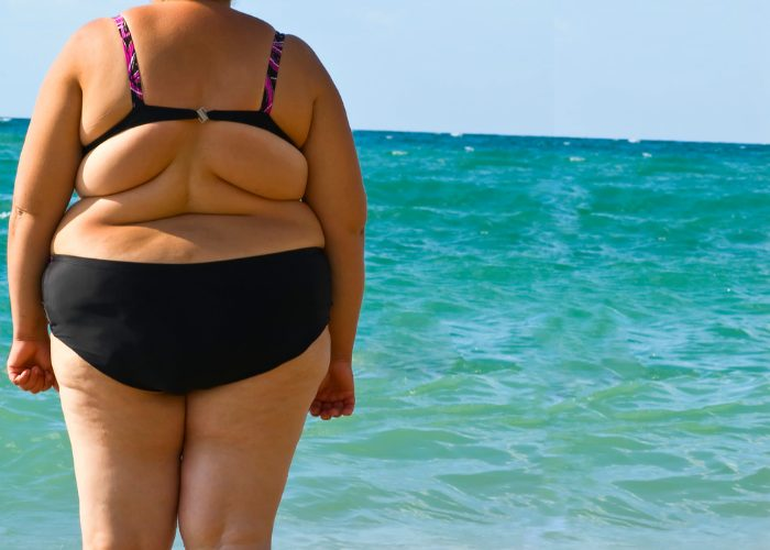 Obese woman in a black bathing suit standing by the sea