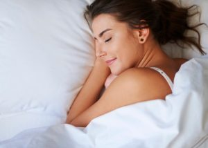 Woman in bed wrapped up in a blanket smiling and having a good night sleep