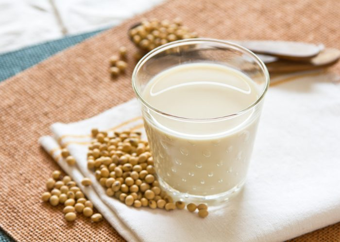a glass of soy milk on white cloth with soybeans next to it