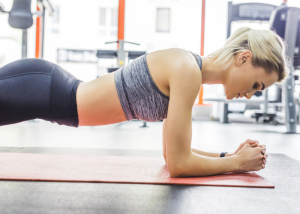 Woman doing planks on a yoga mat  in the gym