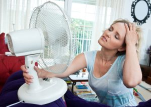 woman in front of a fan looking hot and bothered