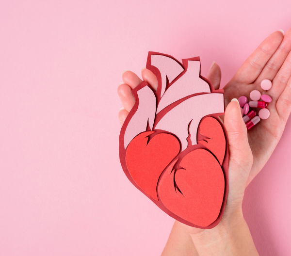 Woman's hands holding a paper cut-out of a human heart in one hand and pills in another