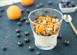 A small glass of homemade yogurt topped with mixed oats, dried fruits, and nuts