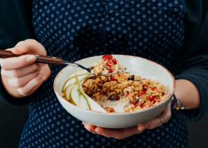 Woman holding a bowl of. homemade yogurt with oats, nuts, and fruits