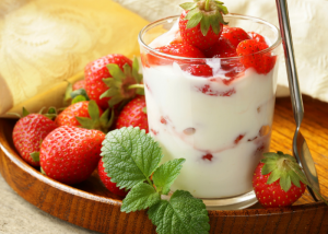 A glass of DIY yogurt with strawberries, served on a wooden tray filled with fresh strawberries
