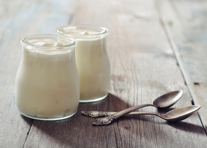 Two small, clear jars of homemade yogurt with two teaspoons next to them on a wooden table