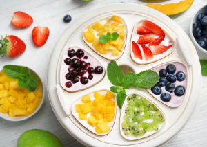 Top down view of yogurt maker with different fruit toppings on the yogurts