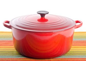 Red dutch oven on a colorful tablecloth