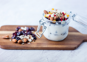 A jar of homemade yogurt on a wooden board, topped with different dried fruits and nuts