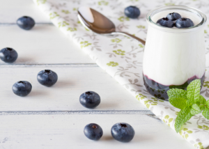 A glass of homemade yogurt with blueberries and blueberry puree