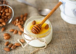 A small jar of homemade yogurt topped with honey and whole almonds, with a honey dipper on the top of the jar, and almonds spilled next to it