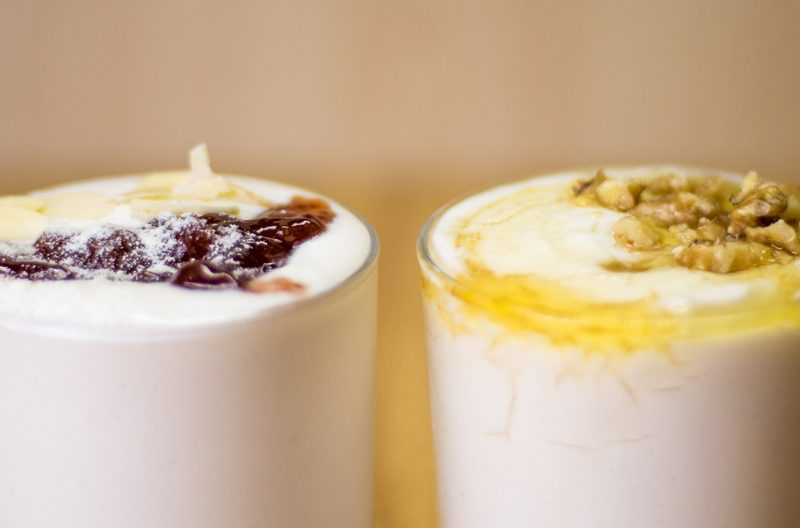 Two glasses of homemade coconut yogurt with different toppings