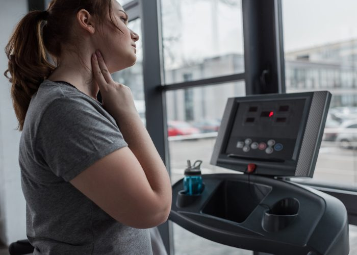Woman checking her pulse after running on a treadmill