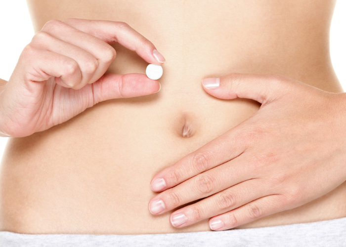 Close up of a woman's abdomen and her holding a white pill with one hand in front of her belly and the other resting on her belly