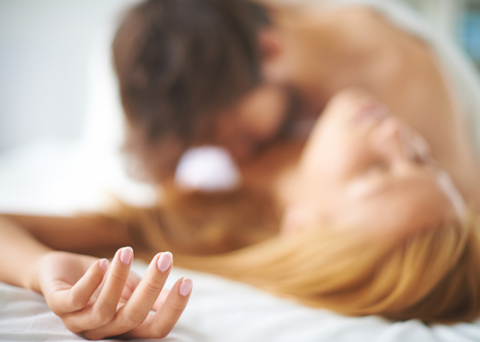 A defocused shot of a couple in bed having sex