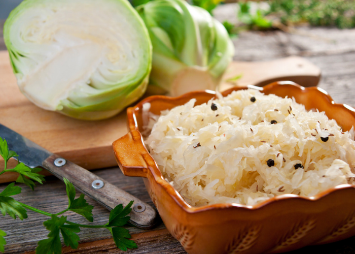 Sauerkraut in a brown ceramic bowl with cabbage halves in the background on a wooden chopping board