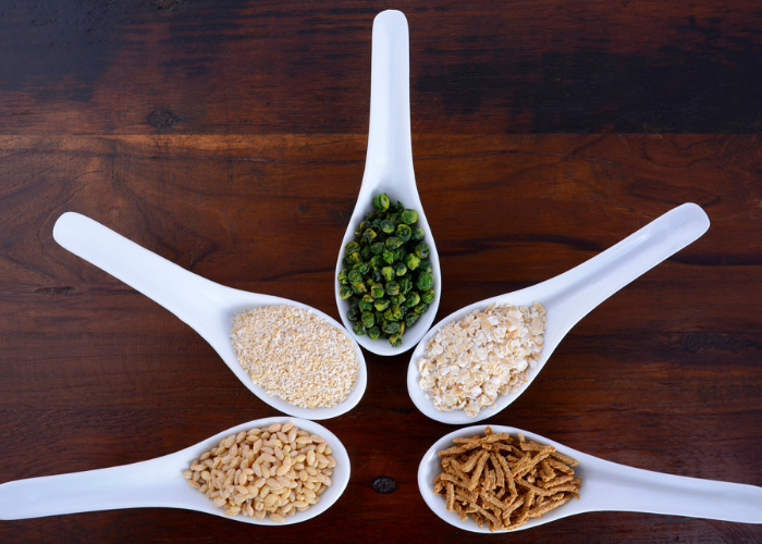Five white soup spoons filled with different prebiotic foods