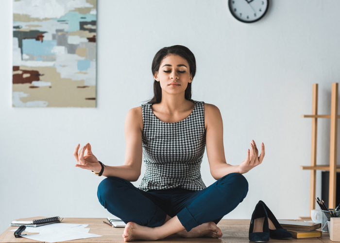 Woman sitting on her work desk with heels off practicing meditation