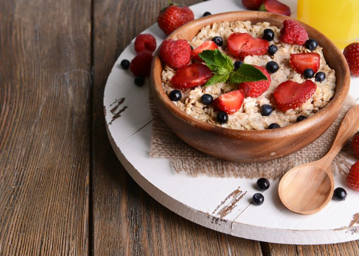 Wooden bowl filled with prebiotic-rich oatmeal, topped with strawberries and blueberries, presented on a white wooden board and wooden spoon