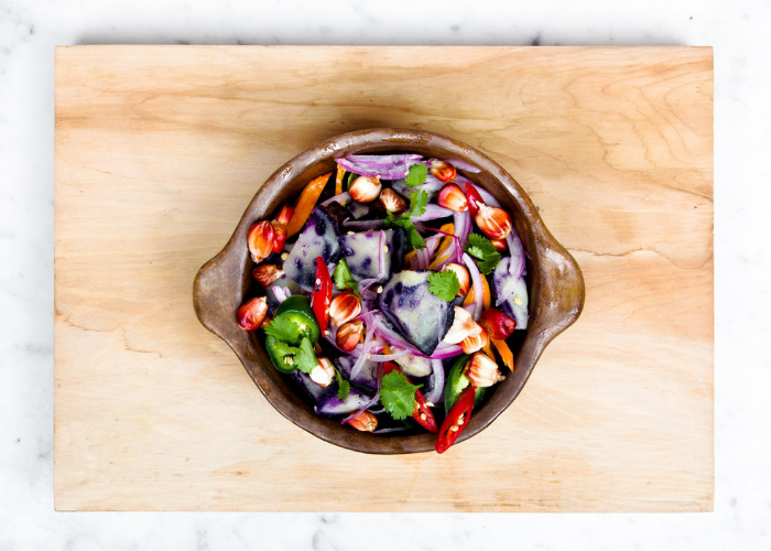 Fresh colorful purple, red, and green vegetables in a dutch oven, on top of a wooden board, set against a light marble background