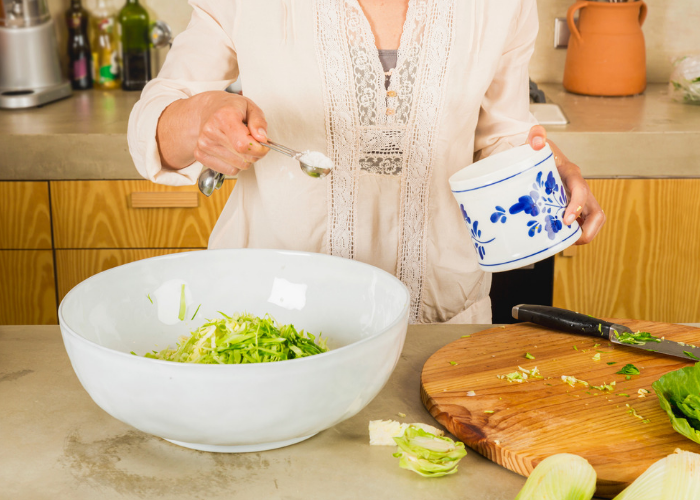 Woman making her own sauerkraut at home pouring sea salt into a large white bowl with sliced cabbage inside