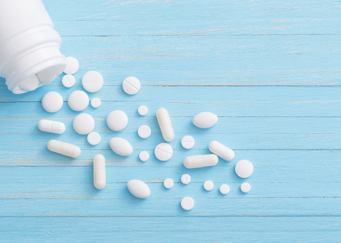An unlabeled medicine bottle spilling out white tablets and capsules of different shapes and sizes on a blue wooden table.