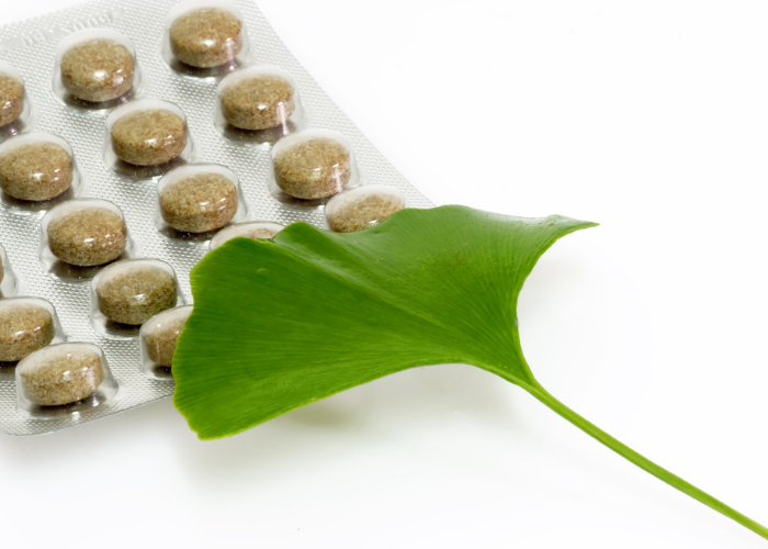 A packet of gingko biloba supplement capsules with a gingko biloba leaf resting on top