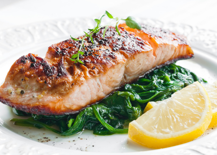 A beautifully presented plate of roast salmon topped with garnish, with a bed of sauteed spinach, and slices of lemon on the side.