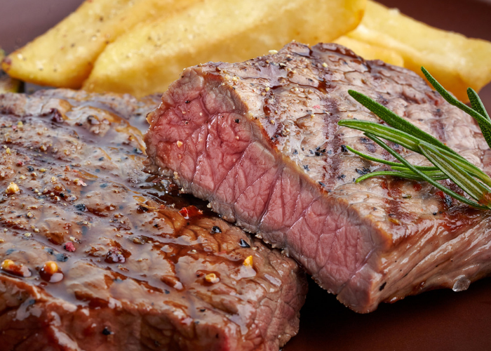 A closeup of juicy medium-rare pepper steak rich in vitamin B12 with a side of French fries