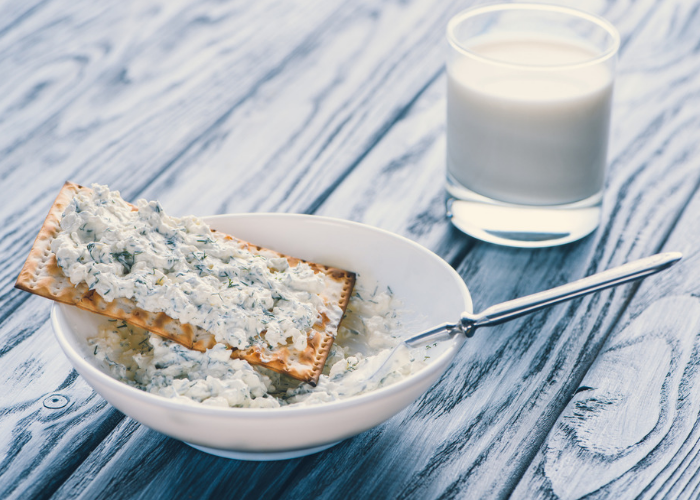 A bowl of blue cheese spread with a cracker on top, with a glass of milk in the background.