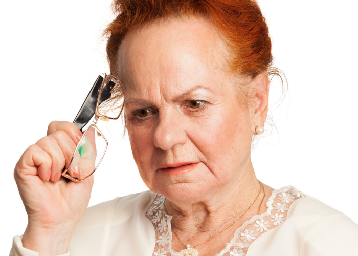 Elderly woman furrowing brow in concentration to recall a distant memory