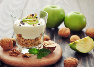 Glass of yogurt with oats, nuts, and green apple, on a wooden dish with walnuts and green apples around it