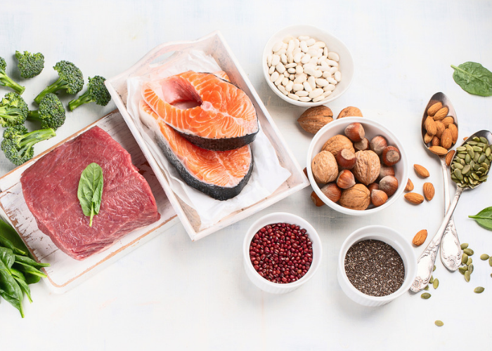 A spread of foods such as meat, fish, nuts, and seeds that are rich in the amino acid isoleucine, laid out on a white table