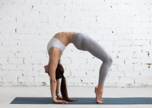 Flexible woman bent backwards in the middle of a yoga practice on a yoga mat